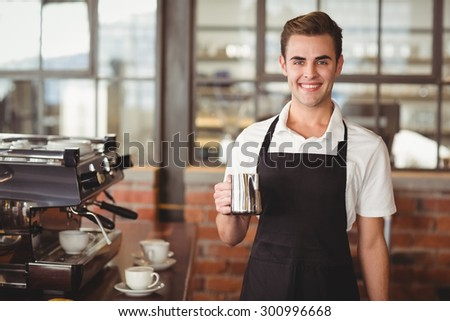Portrait of smiling barista holding jug with milk at coffee shop - stock photo