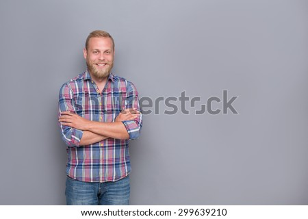Portrait of smiling bearded man with short haircut. Middle-aged man posing with his arms crossed on grey background. - stock photo