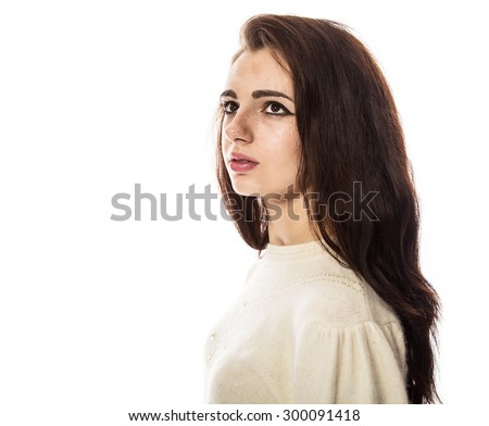 Portrait of smiling beautiful brunette model with freckles and long hair in yellow sweater. Side view. Isolated on a white background. - stock photo