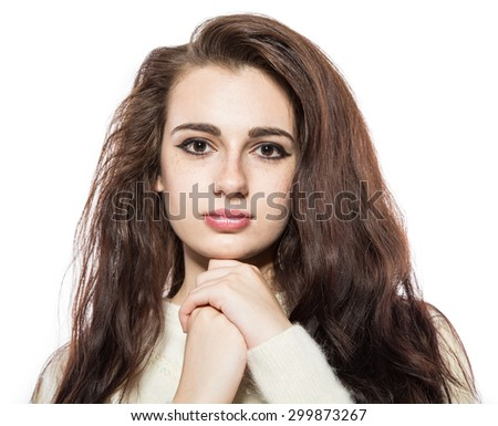 Portrait of smiling beautiful brunette model with freckles and long hair in yellow sweater. With hands on her chin. Isolated on a white background.