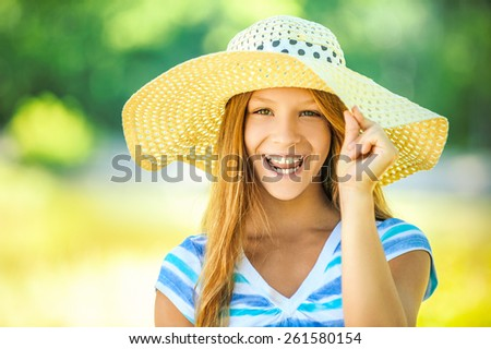 Portrait of smiling beautiful teenage in wide-brimmed hat, against green of summer park. - stock photo