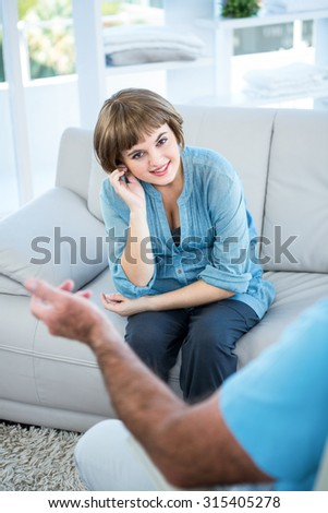 Portrait of smiling beautiful woman sitting in front of father at home
