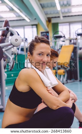 Portrait of smiling beautiful woman with towel resting sitting on the floor of fitness center after hard training day