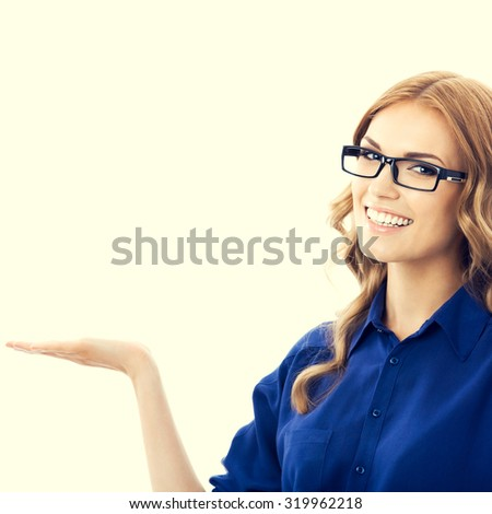 Portrait of smiling beautiful young businesswoman in blue clothing showing something or blank copyspace area for slogan or text message - stock photo