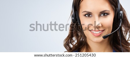 Portrait of smiling beautiful young support phone operator in headset, with copyspace area - stock photo