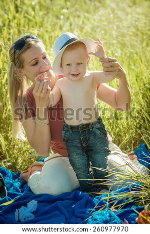 Portrait of smiling beautiful young woman and her little son sitting on grass, against green of summer park. - stock photo