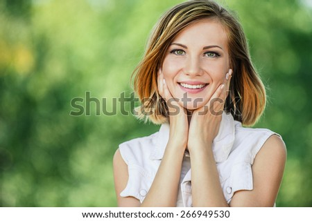 Portrait of smiling beautiful young woman close-up, against green of summer park. - stock photo