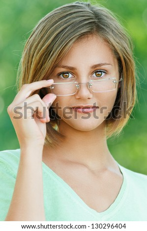 Portrait of smiling beautiful young woman close up with glasses, against background of summer green park. - stock photo