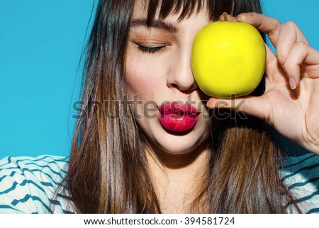 Portrait of smiling beautiful young woman close up with green fresh apple. Blue background. Vegetarian girl on a diet. Healthy food. - stock photo