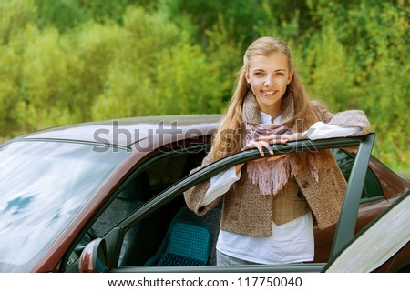 Portrait of smiling beautiful young woman-driver near car, against background of autumn park.