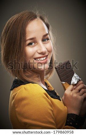 Portrait of smiling beautiful young woman in yellow dress with chocolate bar on dark background. - stock photo