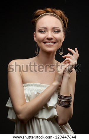 portrait of smiling beautiful young woman on black - stock photo