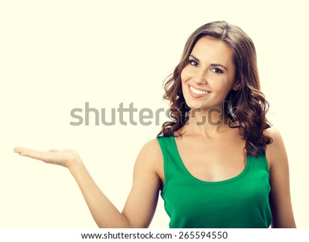Portrait of smiling beautiful young woman showing copyspace or something, in smart green casual clothing - stock photo