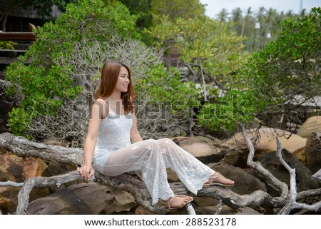Portrait of Smiling beautiful young woman sitting at tree on the