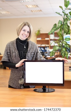Portrait of smiling beautiful young woman with blank computer monitor - stock photo