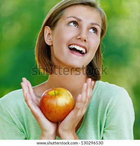 Portrait of smiling beautiful young woman with red apple, against background of summer green park. - stock photo