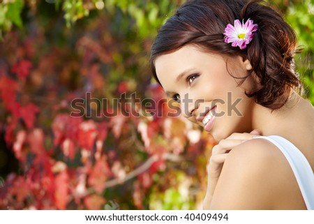 Portrait of smiling beauty against a blossoming garden - stock photo