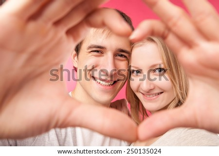 Portrait of smiling beauty girl and her handsome boyfriend making shape of heart by their hands and looking through it. Happy joyful family. Love concept. Heart sign. Laughing happy lovers.  - stock photo