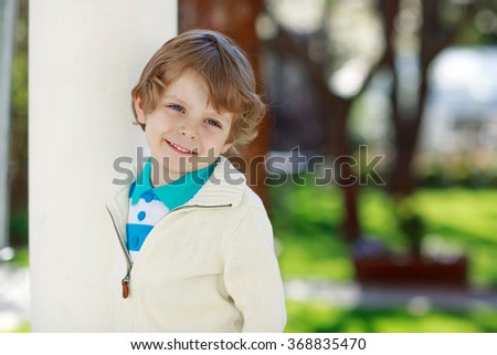Portrait of smiling blond preschool kid boy, outdoors. Happy child looking at camera and smiling on sunny day in spring. Kid in colorful clothes. - stock photo