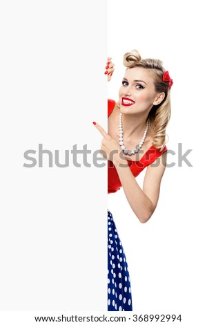 Portrait of smiling blond woman in pin-up style dress, showing blank signboard with copyspace area for slogan or text. Caucasian blond model posing in retro fashion and vintage concept studio shoot. - stock photo