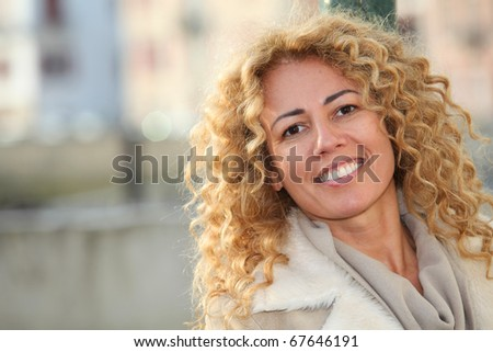 Portrait of smiling blond woman in town - stock photo