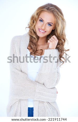 Portrait of Smiling Blond Woman Wearing Cozy Sweater Cardigan in Studio - stock photo