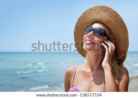 portrait of smiling blond woman with mobile phone on the beach - stock photo