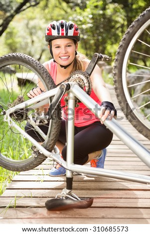 Portrait of smiling blonde athlete checking her mountain bike in the nature