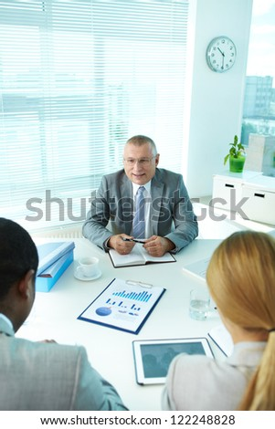 Portrait of smiling boss interacting with his employees - stock photo