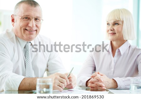 Portrait of smiling boss looking at camera at workplace with mature woman looking at him near by - stock photo