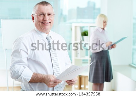 Portrait of smiling boss with papers looking at camera with female standing on background - stock photo