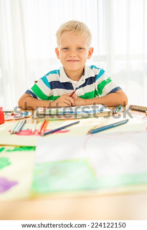 Portrait of smiling boy drawing with pencils