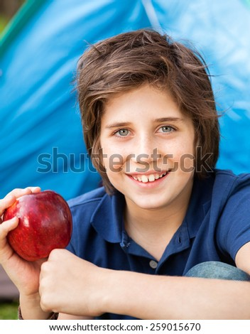 Portrait of smiling boy holding apple at campsite