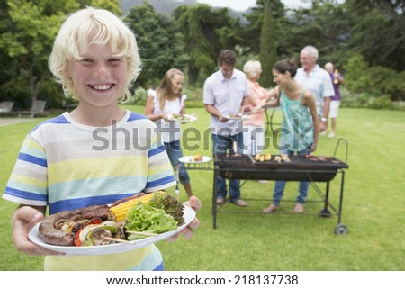 Portrait of smiling boy holding plate of barbecue with family in background - stock photo