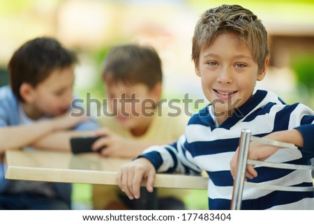 Portrait of smiling boy in cafe with his friends in the background - stock photo