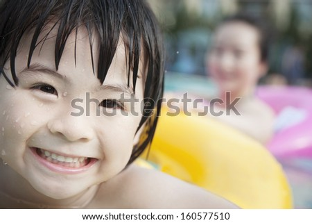 Portrait of smiling boy in pool on inflatable tube with his mother in background - stock photo