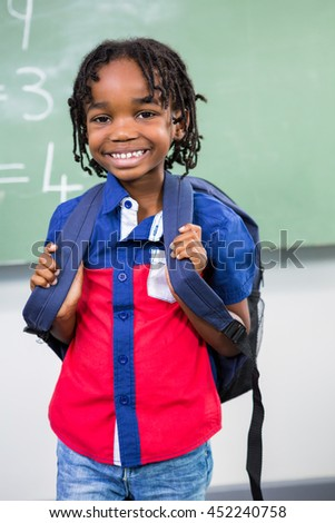 Portrait of smiling boy standing against board in classroom - stock photo
