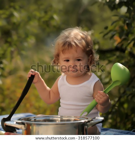 Portrait of smiling boy with blonde curly hair in white underwear holding black and green kitchen utensil and cooking in big pot looking forward outdoor sunny day on natural background, square picture - stock photo