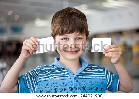 Portrait of smiling boy with two cards in the hands - stock photo