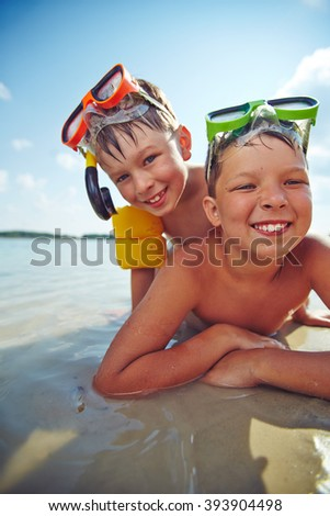 Portrait of smiling boys on the beach - stock photo