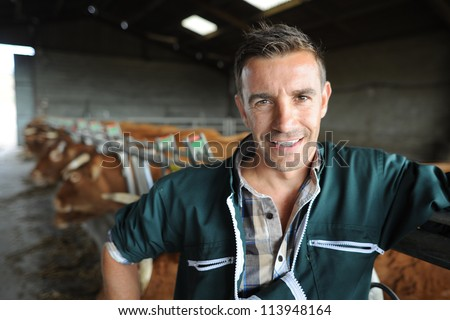 Portrait of smiling breeder in barn - stock photo