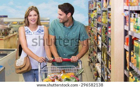 Portrait of smiling bright couple buying food products at supermarket - stock photo