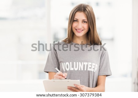 Portrait of smiling brunette volunteer with clipboard in the office