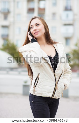 Portrait of smiling brunette wearing white jacket posing with mobile phone outdoors - stock photo