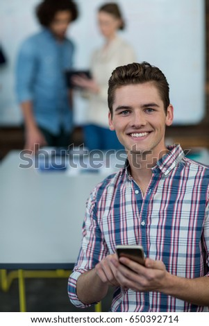 Portrait of smiling business executive using mobile phone in office