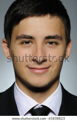 Portrait of smiling business man in formal suit and black tie . expressions on gray background - stock photo