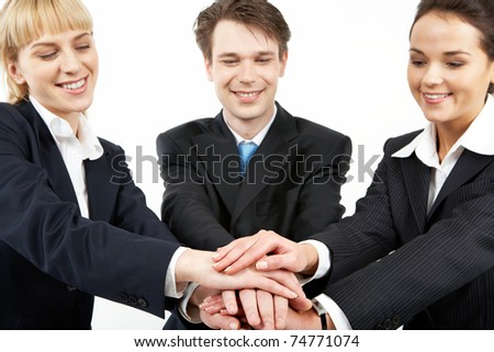 Portrait of smiling business partners with a pile of their hands - stock photo