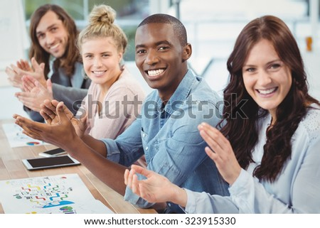 Portrait of smiling business people clapping at desk in office