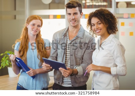 Portrait of smiling business people holding document and digital tablet in office
