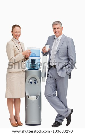 Portrait of smiling business people next to the water dispenser against white background